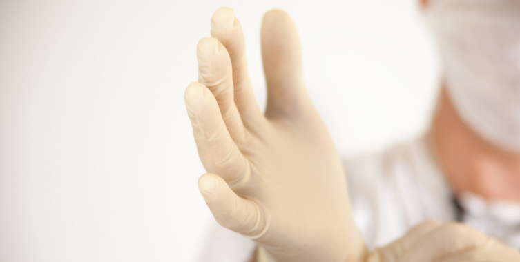 Medical professional puts on a latex glove.