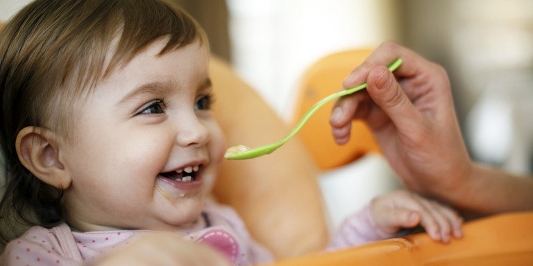 A smiling toddler gets a spoonful of porridge
