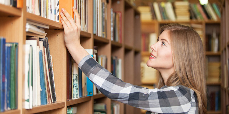 Woman in library, looking for a book
