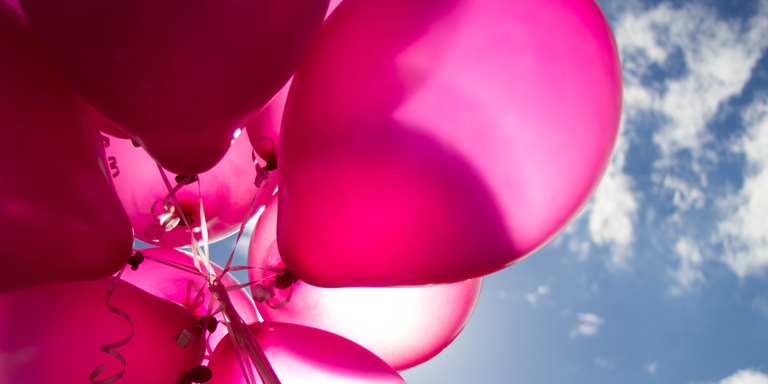 Big pink balloons against a blue sky